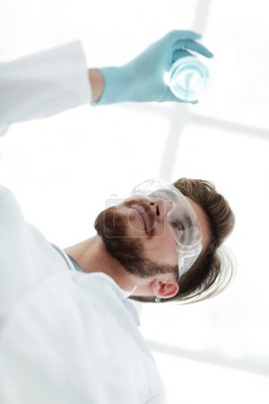 closeup.scientist holding beaker with the sample