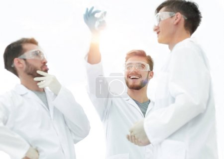 scientists studying the liquid in the beaker.