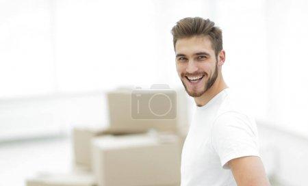 Photo pour Homme souriant debout dans un nouvel appartement.espace de copie de photo - image libre de droit