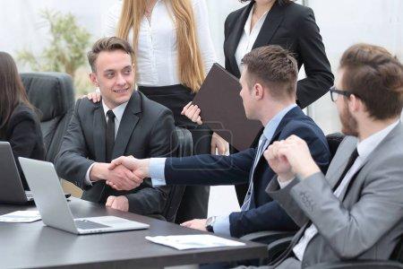 handshake business partners behind a Desk
