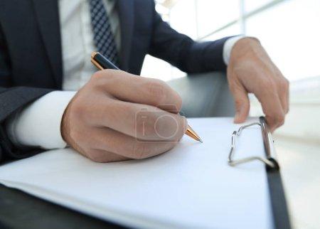 Un homme d'affaires signe un contrat. Stylo de maintien à la main .