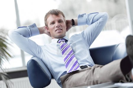 Photo pour Toute la longueur d'un jeune homme d'affaires détendu assis avec les jambes sur le bureau au bureau - image libre de droit