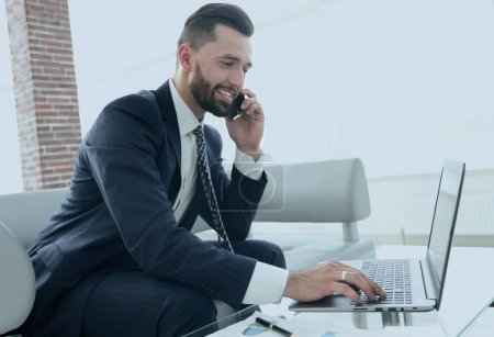 Businessman talking on smartphone and typing text on laptop