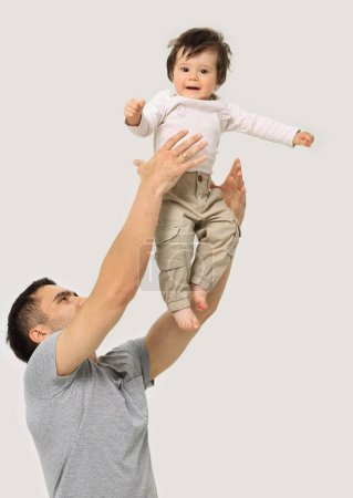 Photo for Father of hand tossing high air joyful boy on isolated background - Royalty Free Image