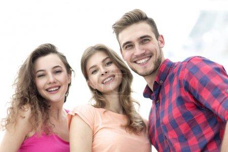 Foto de Closeup de tres personas jóvenes felices sonriendo sobre fondo blanco - Imagen libre de derechos