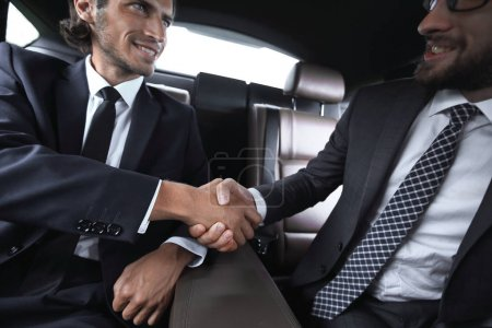 handshake of business partners sitting in the car