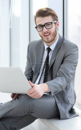 Photo for Employee with a laptop sitting near an office window - Royalty Free Image