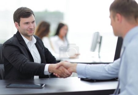 Photo for Handshake business partners at your Desk - Royalty Free Image