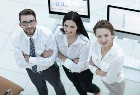 Photo pour Équipe d'affaires réussie debout près du lieu de travail et regardant la caméra . - image libre de droit