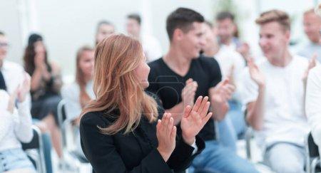 Photo pour En gros plan. une jeune femme souriante applaudissant assise dans une salle de conférence. entreprises et éducation - image libre de droit