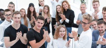Photo pour Vue de dessus. un groupe de jeunes souriants applaudit ensemble - image libre de droit
