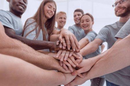 Photo pour De près. un groupe de jeunes qui montrent leur unité. le concept de travail d'équipe - image libre de droit
