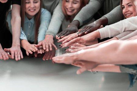 Photo pour De près. un groupe de jeunes souriants unissant leurs mains - image libre de droit