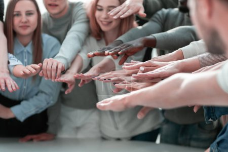 Photo for Close up. a group of smiling young people joining their hands together - Royalty Free Image