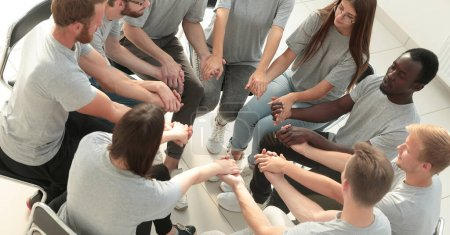 Photo for Top view. young people holding each others hands at a group meeting. - Royalty Free Image
