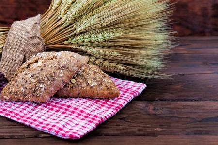 Fresh bread and wheat. Dark background.
