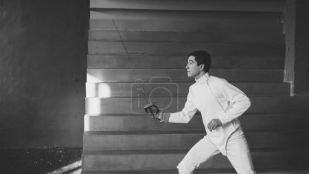 Photo for Concentrated fencer man practice fencing exercises and training for competition in studio indoors - Royalty Free Image