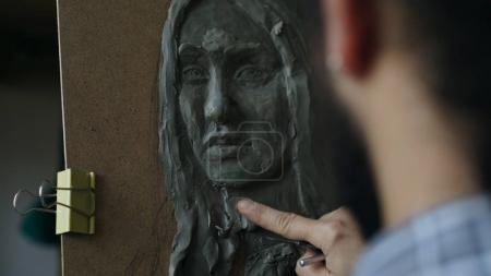 Photo pour Gros plan du sculpteur création sculpture du visage de l'homme sur la toile dans le studio d'art à l'intérieur - image libre de droit