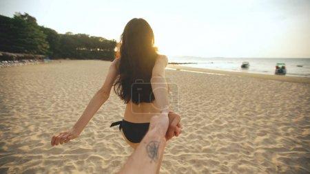 Photo pour Suivez-moi photo de jeune fille sexy en bikini courant et tenant la main de l'homme sur la plage au coucher du soleil. heureux couple avoir amusant et sourire - image libre de droit