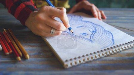 Photo pour Gros plan de croquis de peinture à la main féminine sur carnet de papier avec crayons. Femme artiste au travail en studio à l'intérieur - image libre de droit