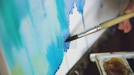 Photo pour Jeune femme artiste dessiner pictrure avec aquarelle peintures et pinceau sur chevalet toile gros plan main en studio à l'intérieur - image libre de droit
