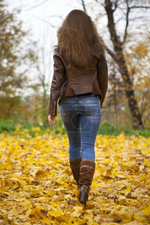 Autumn fashion image of young woman walking in the park