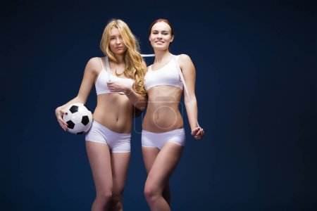 Two Young beautiful women in white fitness clothing