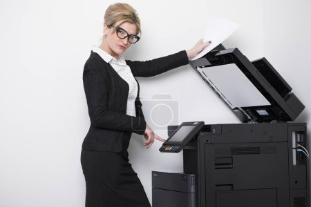 Young beautiful woman making copies in the office