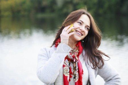 Portrait of happy young brunette woman in beige coat talking on