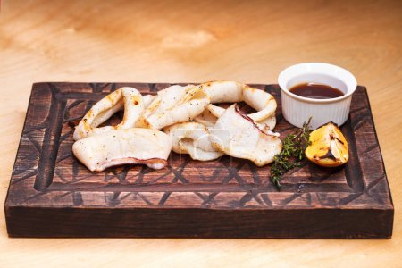 grilled squid rings on a wooden board with sauce