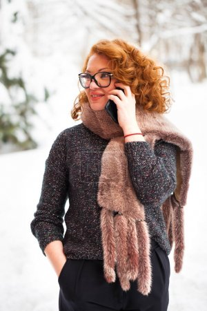 Beautiful redhair woman calling on a cell phone