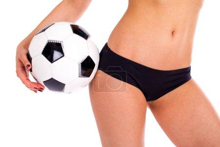 Soccer ball and feminine hips. Black Underwear. Close up photo o