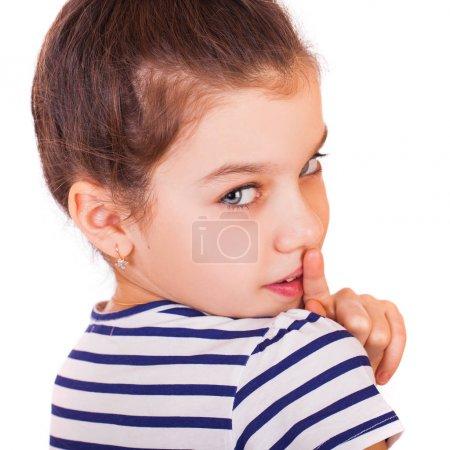 Photo pour Belle petite fille brune a mis à l'index sur les lèvres comme signe du silence, isolé sur fond blanc - image libre de droit