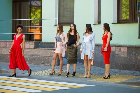 Street Fashion. Five beautiful fashionable girlfriends walk in sunny weather in the city
