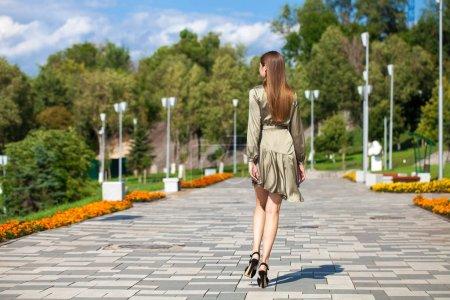 Photo pour Verticale de vue arrière en pleine croissance, jeune belle femme brune dans une robe verte marchant sur la rue - image libre de droit
