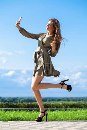 Photo pour Verticale en pleine croissance, jeune belle femme brune dans une robe verte marchant sur la rue, été à l'extérieur - image libre de droit