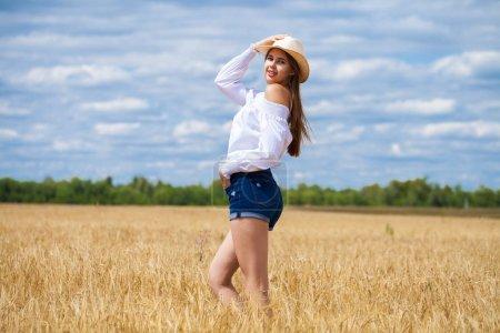 Photo pour Verticale d'une jeune femme brune dans la chemise blanche et les shorts de jeans sur un fond de champ de blé d'or, l'été à l'extérieur - image libre de droit