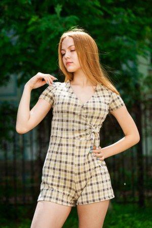 Photo pour Gros plan portrait d'une jeune belle femme rousse en robe à carreaux beige - image libre de droit