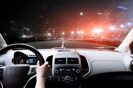 Photo pour Pilotes des mains sur le volant à l'intérieur de la voiture sur la route goudronnée - image libre de droit