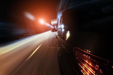 Photo pour Voiture rapide noire à la rue de ville de nuit - image libre de droit