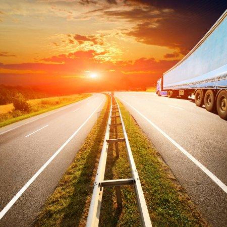 Photo pour Camion bleu sur l'autoroute palpite les champs d'été - image libre de droit