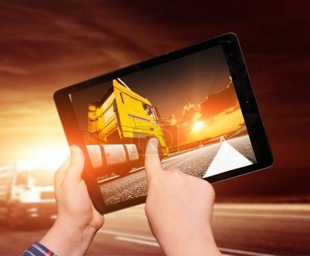 Tablet in hands with image of truck