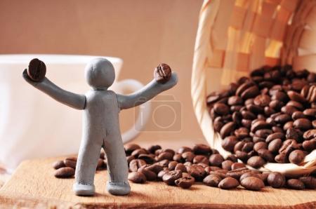 Plasticine man holding coffee beans