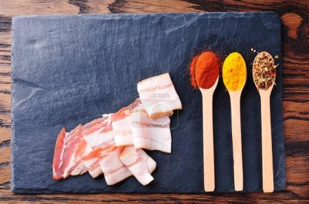 Bacon slices and spoons with spices