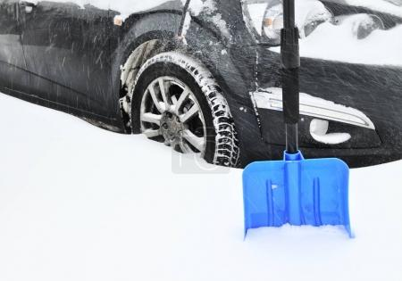 Black car under intensive snowfall stuck in snowdrift and blue shovel