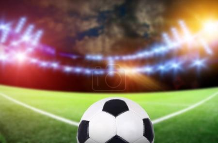 Ball on soccer stadium with bright lights under blurred cloudy sky