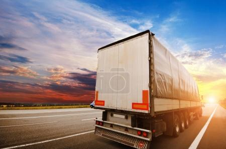 Big semi truck with a white trailer on countryside road against sky with beautiful sunset