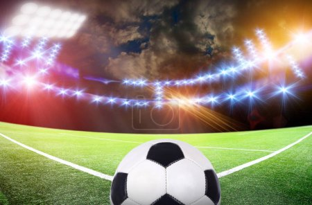 Ball on soccer stadium with bright lights under cloudy sky
