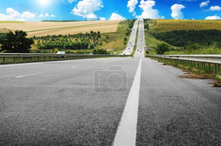 Asphalt countryside road with woods and fields against blue sky with white clouds and sun