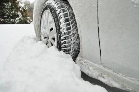 Car front wheel stuck in snow in forest